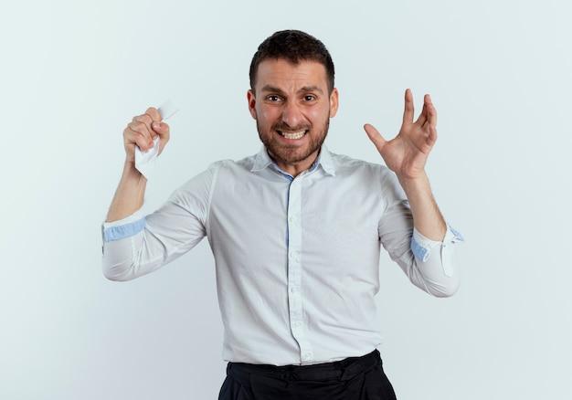 Uomo bello furioso preme carta in pugno e stringe la mano isolata sul muro bianco