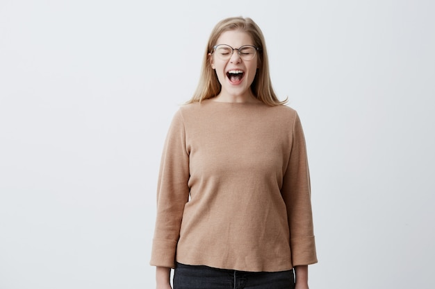 Furious irritated young woman screams in despair, frowns face, being disturbed by something, quarrels with someone, confident in her rightness. angry blonde female in glasses yells