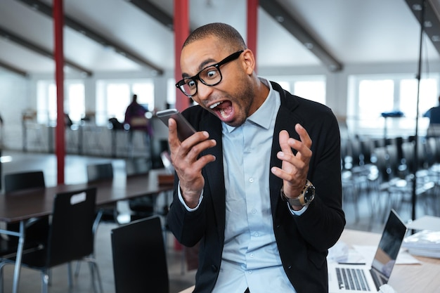Furious mad bisnessman talking shouting on the phone in the office