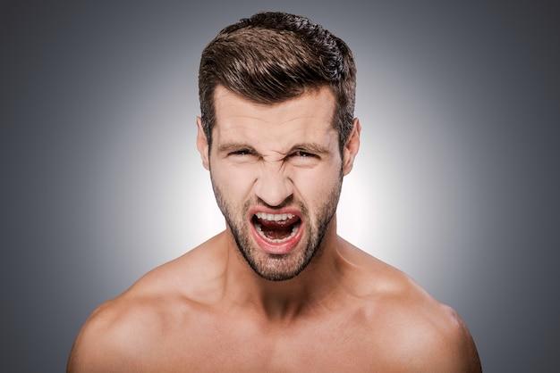 분노한 남자. 회색 배경에 서서 카메라를 바라보고 입을 벌리고 있는 화난 젊은 남자의 초상화