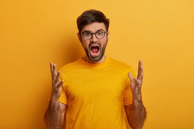 격노 한 남자는 분노로 소리 지르고 몸짓을하며 입을 벌리고 있습니다.