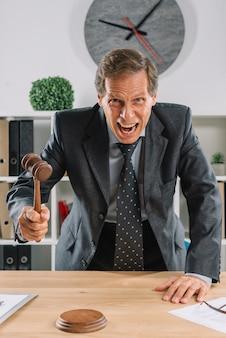 Яростный зрелый адвокат, дающий вердикт, ударяя молотком на стол
