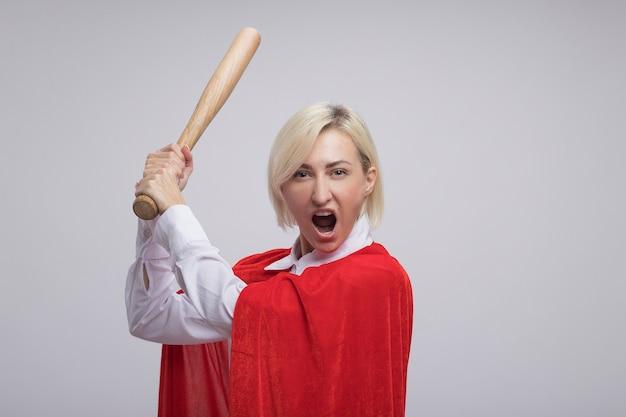 Furiosa donna di mezza età bionda supereroe in mantello rosso che alza la mazza da baseball guardando la parte anteriore isolata sul muro bianco con spazio di copia