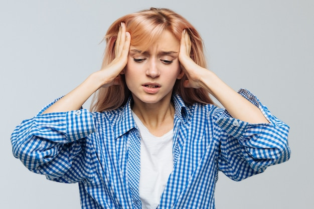 У бешеной или стрессовой подростковой женщины болит голова, она пытается сосредоточиться, собраться с мыслями, держит руки на висках