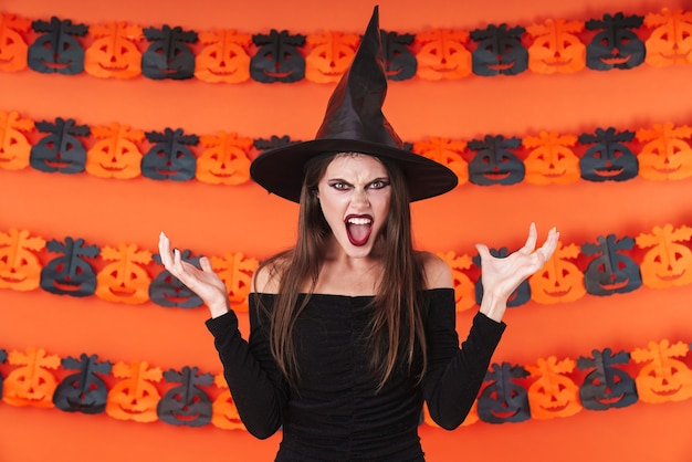 Furious witch girl in black halloween costume standing with arms crossed isolated over orange pumpkin wall