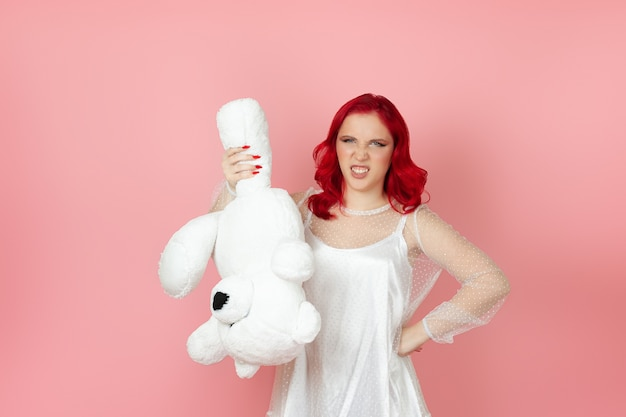 Furious woman in a white dress and red hair holds a large white teddy bear upside down by the paw and bares her teeth