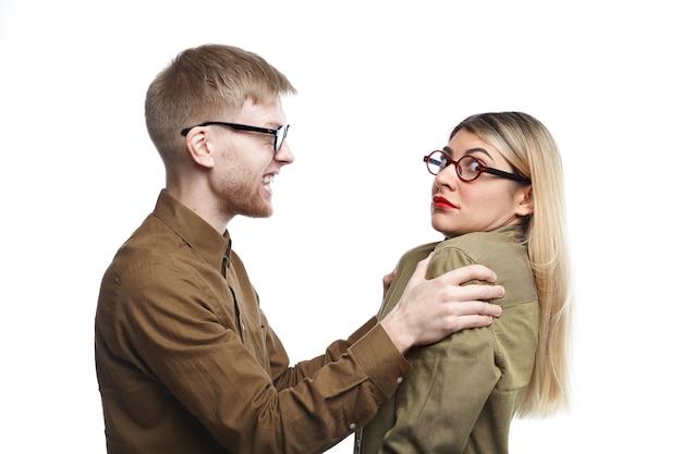 眼鏡をかけた猛烈な若いあごひげを生やした男性が、おびえた妻を肩で振っています。怒った夫に虐待されている眼鏡をかけた怖い女性。人、結婚、虐待、家庭内暴力の概念