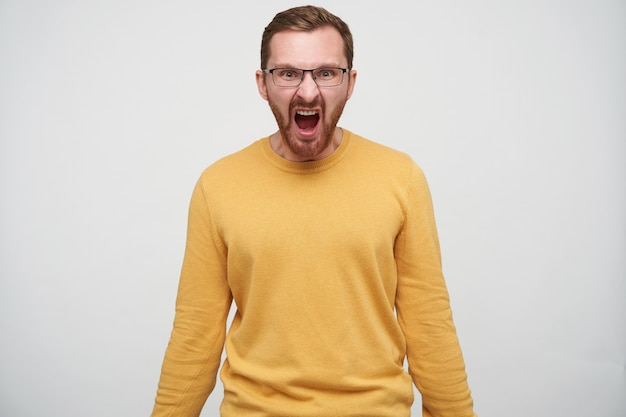 Furious young bearded male with brown short hair looking and screaming violently with wide mouth opened, dressed in mustard pullover while standing
