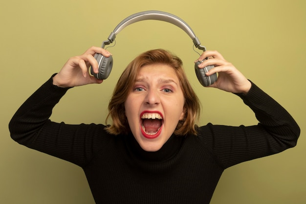 Furious young blonde girl holding headphones