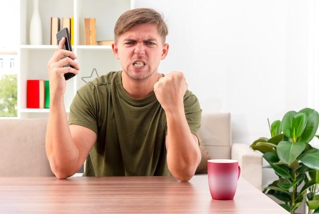 분노한 젊은 금발의 잘 생긴 남자는 컵이 전화를 들고 거실 안에 주먹을 유지하면서 테이블에 앉아있다.