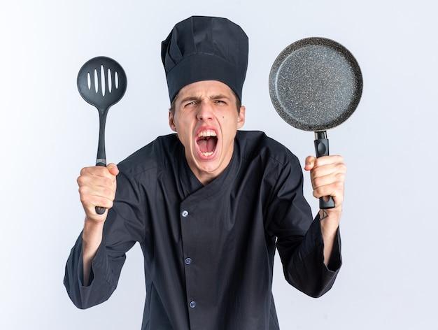 화난 젊은 금발 남성 요리사 유니폼을 입고 모자를 쓰고 주걱과 프라이팬을 보여주는 카메라를 쳐다보며 흰 벽에 고립되어 비명을 지르고 있다