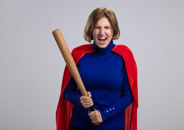 Giovane ragazza bionda furiosa del supereroe in mantello rosso che tiene la mazza da baseball che grida isolato sulla parete bianca con lo spazio della copia