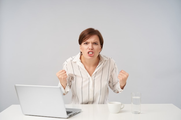 猛烈な若い茶色の髪の女性は、短い流行のヘアカットで拳を握りしめ、激しく見ながら顔をしかめ、縞模様のシャツを着て白でポーズをとる