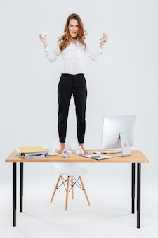 Furious young businesswoman standing on table and throwing paper over white background