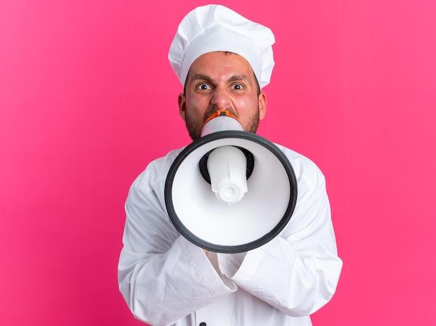Разъяренный молодой кавказский повар в униформе шеф-повара и кепке смотрит в камеру, кричит в громкоговоритель, изолированную на розовой стене