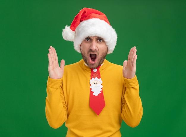Разъяренный молодой кавказский человек в рождественской шляпе и галстуке смотрит в камеру, держа руки в воздухе, крича, изолирован на зеленом фоне