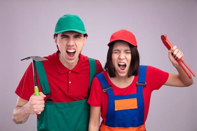 Furioso giovane coppia in operaio edile uniforme e cap ragazza alzando la chiave a tubo con gli occhi chiusi ragazzo che tiene la zappa-rastrello entrambi urlando