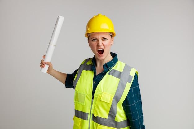 Furioso giovane operaio edile femminile che indossa il casco di sicurezza e giubbotto di sicurezza che tiene carta gridando ad alta voce