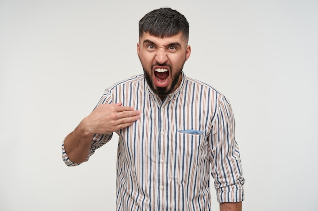 Furious young handsome dark haired man with beard pointing on himself with raised palm and shouting angrily while looking , isolated over white wall