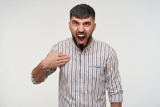 Furioso giovane bell'uomo dai capelli scuri con la barba che punta su se stesso con il palmo sollevato e grida con rabbia mentre guarda, isolato sopra il muro bianco