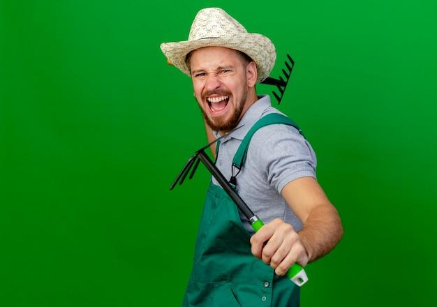 Разъяренный молодой красивый славянский садовник в форме и шляпе смотрит с граблями и граблями
