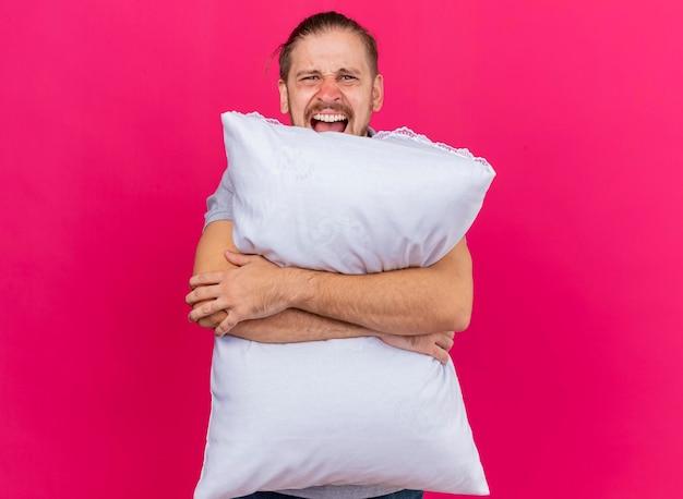 Furioso giovane bello slavo malato abbracciando cuscino guardando davanti urlando isolato sulla parete rosa con copia spazio