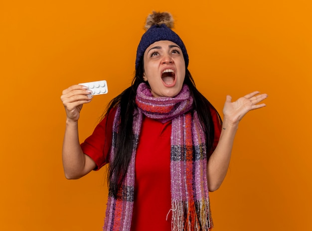 겨울 모자와 스카프를 착용하는 분노한 젊은 아픈 여자는 빈 손을 보여주는 태블릿의 팩을 들고 오렌지 벽에 고립 된 비명