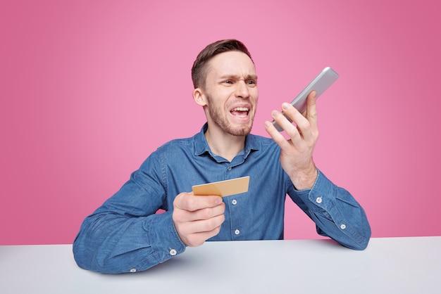 Разъяренный молодой мужчина-покупатель кричит в смартфон, жалуясь на качество доставленных товаров из интернет-магазина