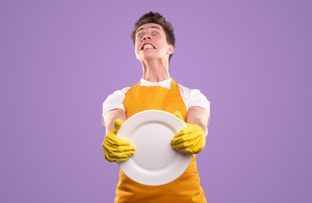 黄色いエプロンと手袋をはめて、家事を代表しながら透明な白い皿を持った猛烈な青年