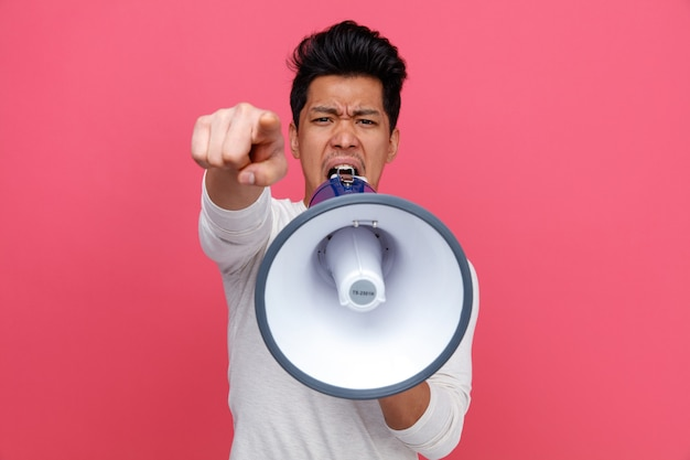 Furious young man looking and pointing at camera shouting in loud speaker