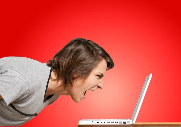 ノートパソコンで叫んで猛烈な若い男