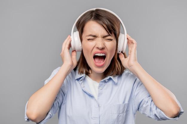 Разъяренная молодая женщина в наушниках громко кричит во время пения песни или выражает раздражение