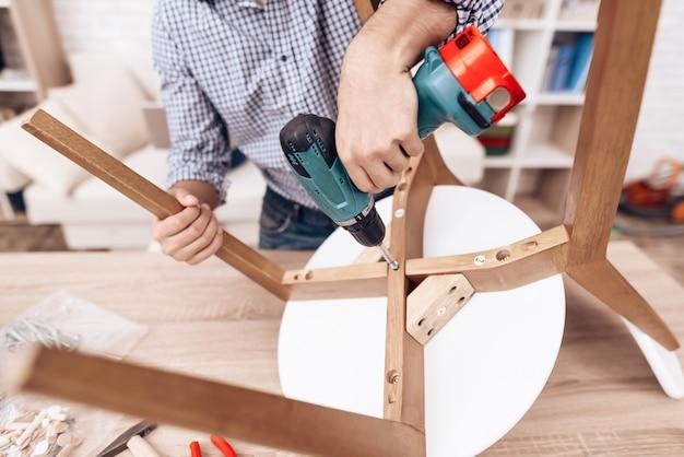 手でドリルで家具アセンブラーは椅子を修理します。