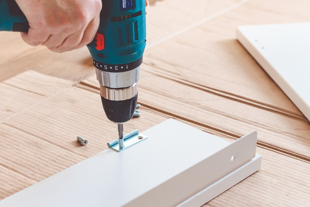 Furniture assembling using battery drill on white background.