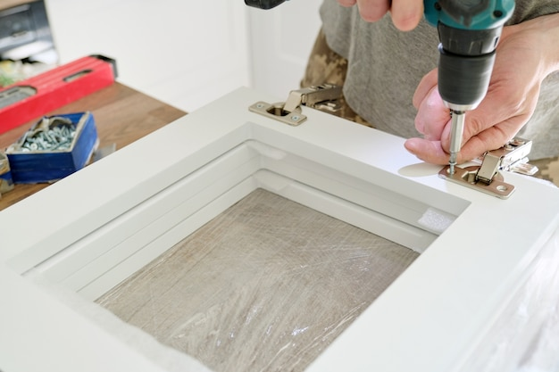Сборка мебели, завинчивание хромированных дверных петель крупным планом профессиональным инструментом