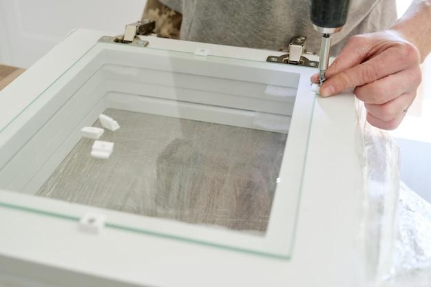 家具の組み立て。プロのツールと家具の詳細と労働者の手のクローズアップ