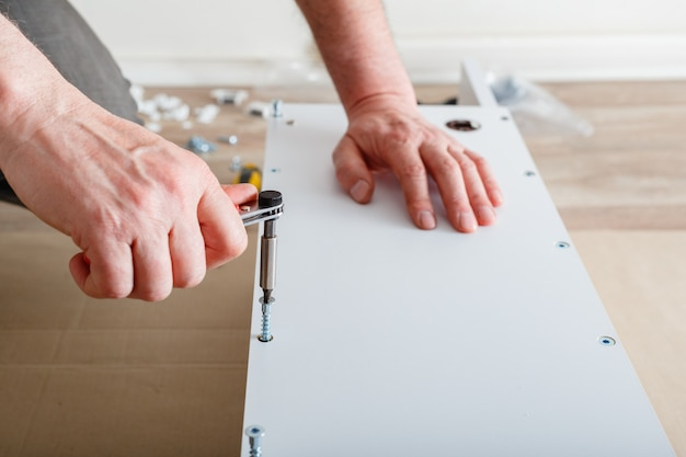 Furniture assembly male hands master collects furniture using screwdriver tools instrument at home m...