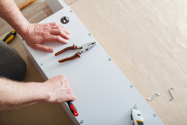 Furniture assembly. male hands master collects furniture using screwdriver tools, instrument at home. moving, home improvement, furniture repair and renovation. copy space.