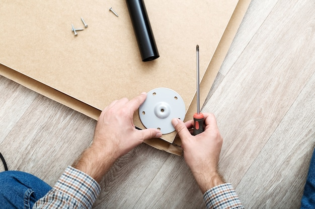 Furniture assembly using screwdriver. male hands master collects furniture using screwdriver tools, instrument at home. moving, home improvement, furniture repair and renovation.