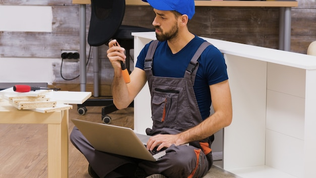 Furniture assembly worker wearing overalls searching instructions using his laptop. worker holding screwdriver.