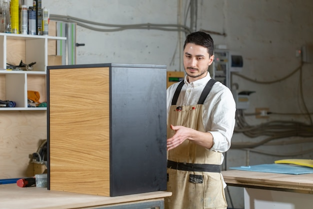 Furniture factory and small and medium sized enterprises concept - man collects furniture details