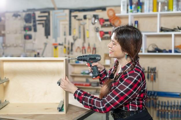 Мебельная фабрика, малые компании и концепция работницы - женщина с дрелью на
