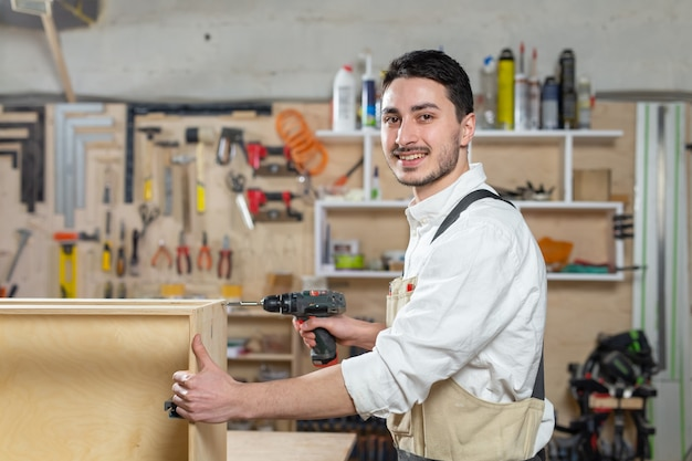 Мебельная фабрика, малые компании и концепция людей - молодой рабочий работает на фабрике по производству мебели.