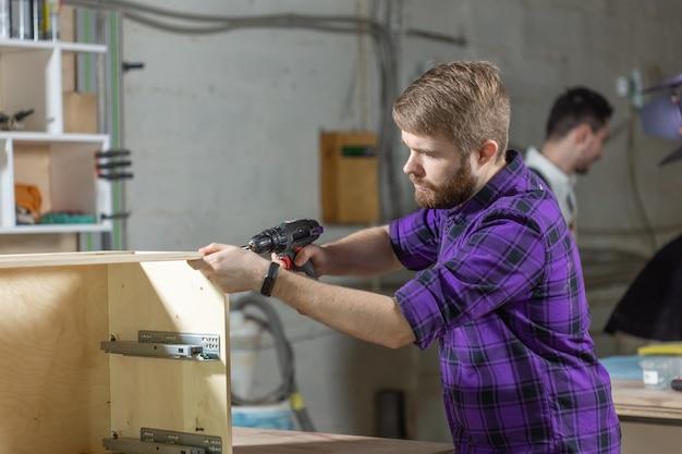 가구 공장, 중소기업 및 사람들 개념-젊은 노동자는 가구 생산을 위해 공장에서 일합니다.