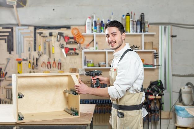 Мебельная фабрика, малые компании и концепция людей - молодой рабочий работает на фабрике для