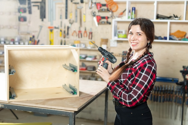 Furniture factory, small-sized companies and female worker concept - woman with a drill on the factory.