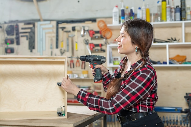Furniture factory, small-sized companies and female worker concept - woman with a drill