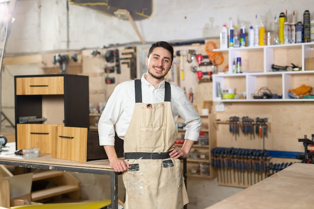 Furniture factory, small-sized companies and people concept - portrait of a smiling male worker at manufacturing