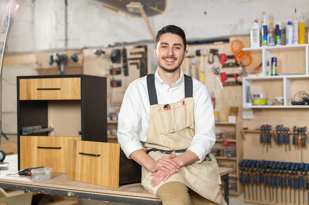 Furniture factory, small-sized companies and people concept - portrait of a smiling male worker at