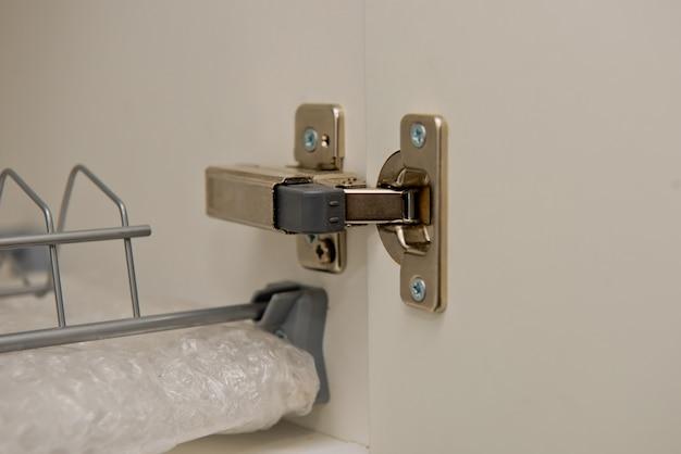 Мебельная петля установлена в кухонном ящике. закройте вверх. мебельная фурнитура. петля на дверце шкафа.